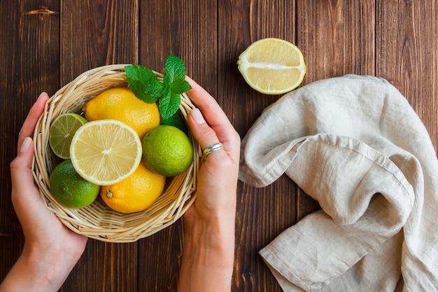 Conjunto de mão de pano branco segurando a cesta de limão e limões em uma cesta sobre uma superfície de madeira. vista do topo.