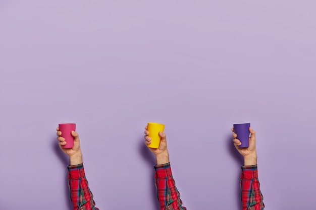 Conjunto de mãos masculinas com copos plásticos vazios coloridos