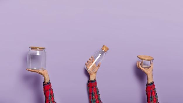 Conjunto de mãos masculinas segurando uma jarra de vidro vazia, garrafa e recipiente com tampa orgânica