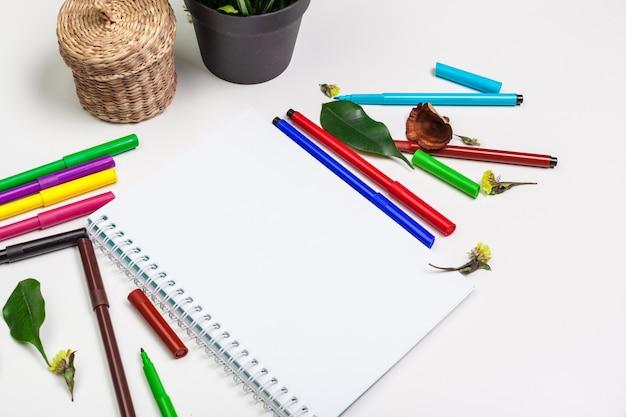 Conjunto de marcadores de ponta de feltro em cores diferentes e um caderno em branco com um espaço para texto