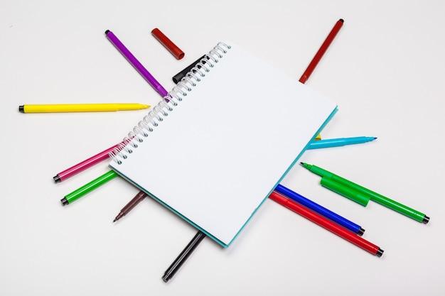 Conjunto de marcadores de ponta de feltro em cores diferentes e um caderno em branco
