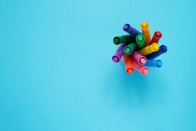 Conjunto de marcadores em um copo e em azul claro. vista do topo. volta ao conceito de escola