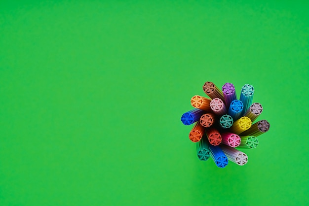 Conjunto de marcadores em um suporte e no fundo de néon verde brilhante. vista do topo. volta ao conceito de escola