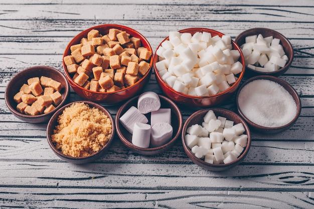 Conjunto de marshmallow e açúcar branco e marrom em taças sobre uma mesa de madeira clara. vista de alto ângulo.