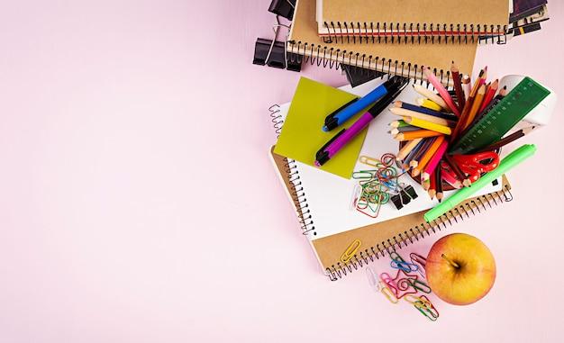 Conjunto de material escolar colorido, livros e cadernos. acessórios de papelaria. vista do topo.