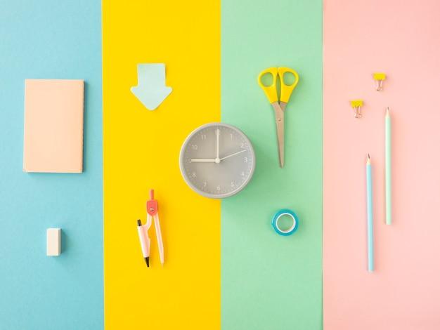 Conjunto de material escolar e papelaria sobre superfície colorida