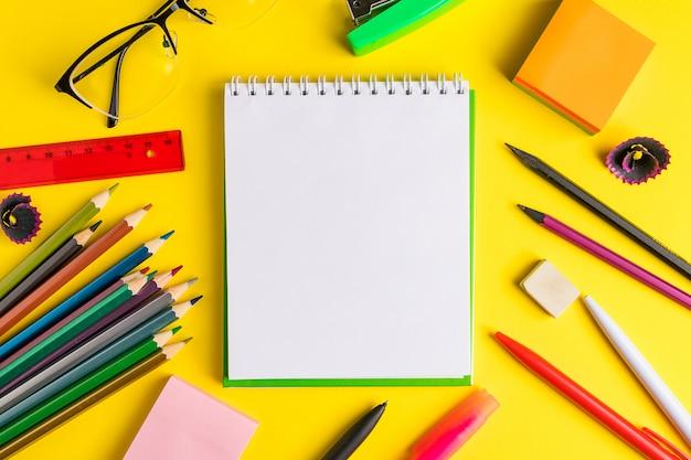 Conjunto de material escolar em fundo amarelo.
