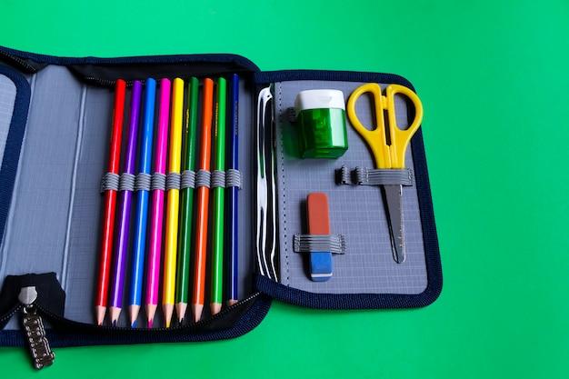 Conjunto de material escolar em uma caixa de lápis sobre um fundo verde de papel com espaço de cópia para o texto.