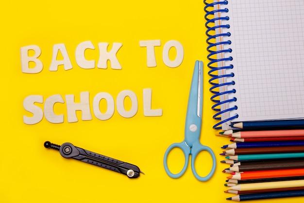 Conjunto de material escolar na mesa amarela com a inscrição