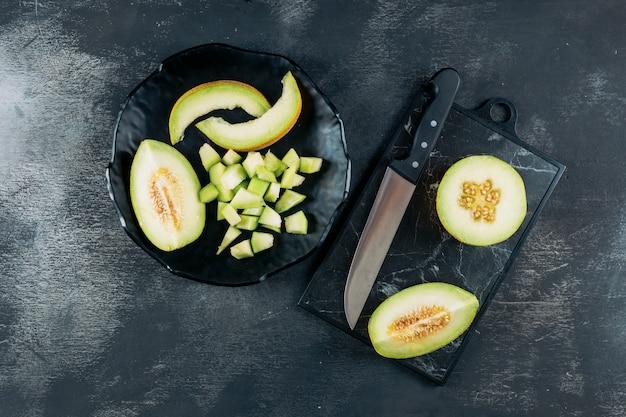 Conjunto de melão e faca e melão fatiado em uma tigela preta sobre um fundo escuro de madeira. configuração plana.