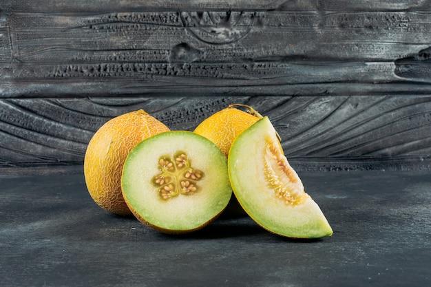 Conjunto de melão e melão fatiado em um fundo escuro de madeira. vista lateral.