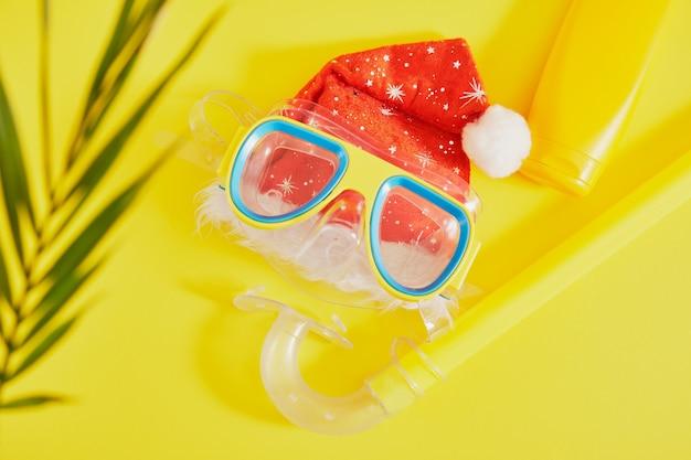 Conjunto de mergulho, chapéu de papai noel e protetor solar em fundo amarelo, férias de natal na praia em uma vista panorâmica do campo quente