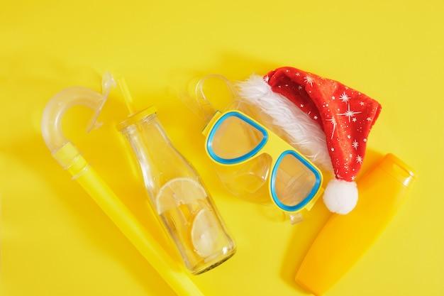 Conjunto de mergulho, chapéu de papai noel, protetor solar e uma garrafa de limonada, férias de natal na praia em um país quente
