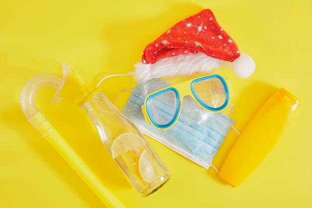 Conjunto de mergulho, máscara médica protetora, chapéu de papai noel, protetor solar e uma garrafa de limonada em um fundo amarelo, férias de natal em um país quente durante uma pandemia