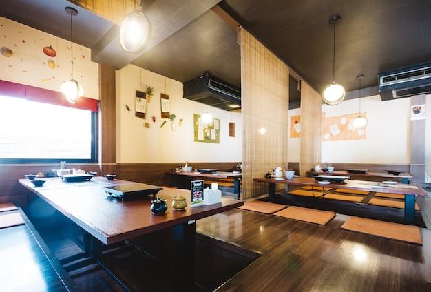 Conjunto de mesa de jantar shabu incluindo uma mesa de madeira e assentos no chão com teto de bambu.