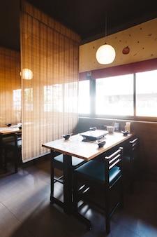 Conjunto de mesa de jantar shabu incluindo uma mesa de madeira e quatro lugares com teto de bambu para privacidade.