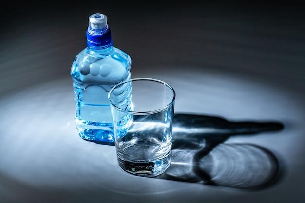 Conjunto de mesa servida de garrafa de água mineral e vidro
