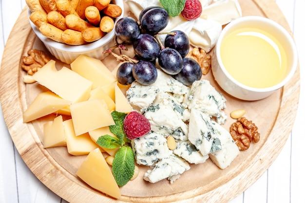 Conjunto de mistura de queijos com queijo brie de parmesão blu chedar e uva em wooren palte