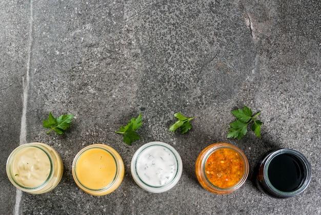 Conjunto de molhos dietéticos saudáveis orgânicos para salada: molho vinagrete, mostarda, maionese com especiarias ou rancho, balsâmico ou soja, manjericão com iogurte. em uma mesa de pedra escura. espaço de cópia da vista superior