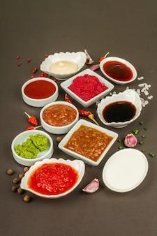 Conjunto de molhos diferentes - ketchup, maionese, churrasco, soja, chutney, wasabi, adjika, raiz-forte, aioli, marinara. fundo de concreto de pedra escura, close-up