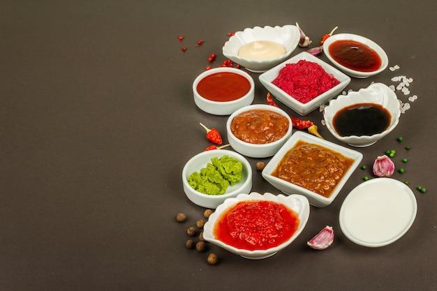 Conjunto de molhos diferentes - ketchup, maionese, churrasco, soja, chutney, wasabi, adjika, raiz-forte, aioli, marinara. fundo de concreto de pedra escura, copie o espaço