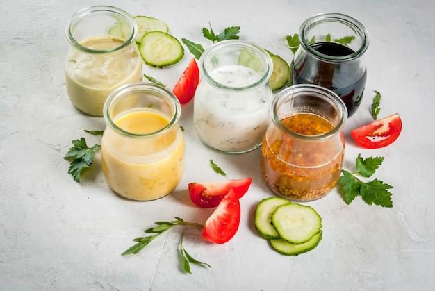 Conjunto de molhos para salada: molho vinagrete, mostarda, maionese ou rancho, balsâmico ou soja, manjericão com iogurte. mesa de concreto branca escura, com hortaliças, legumes para salada. copie o espaço