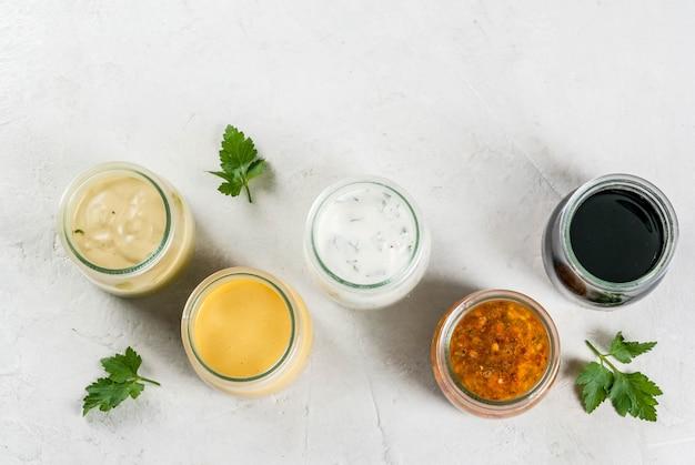 Conjunto de molhos para salada: molho vinagrete, mostarda, maionese ou rancho, balsâmico ou soja, manjericão com iogurte. mesa de concreto branca escura. vista superior do espaço da cópia