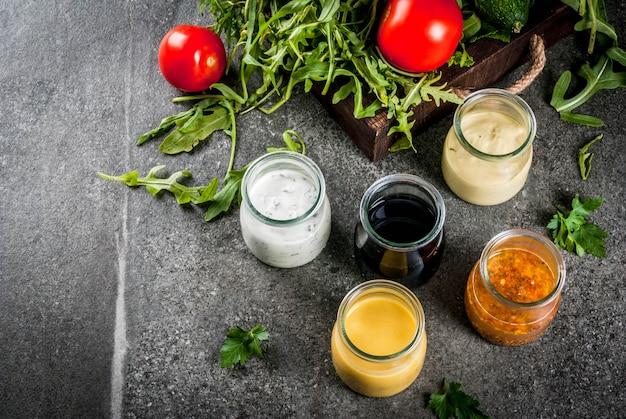 Conjunto de molhos para salada: molho vinagrete, mostarda, maionese ou rancho, balsâmico ou soja, manjericão com iogurte. mesa de pedra escura.