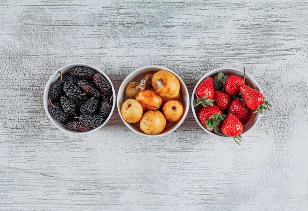 Conjunto de morangos, amoras e nêsperas em uma tigela sobre um fundo claro de madeira. vista do topo. espaço para texto