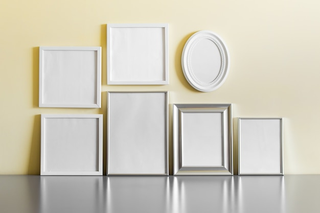 Conjunto de muitos prata metálicos em branco e armações de madeira brancas na parede amarela.