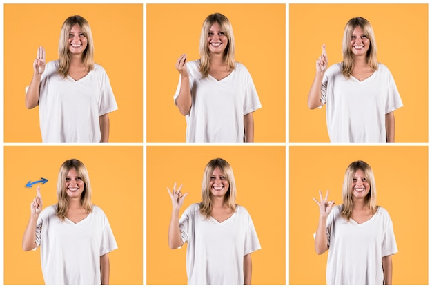 Conjunto de mulher feliz mostrando sinal surdo contra parede amarela