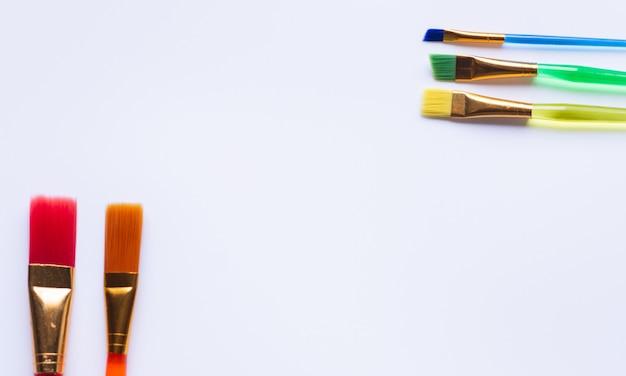 Conjunto de novos pincéis coloridos e tintas em fundo branco, com espaço de cópia
