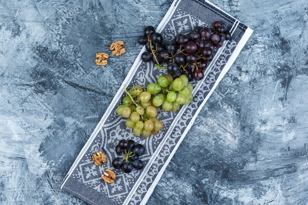 Conjunto de nozes e cachos de uva em grunge e fundo de toalha de cozinha. colocação plana.