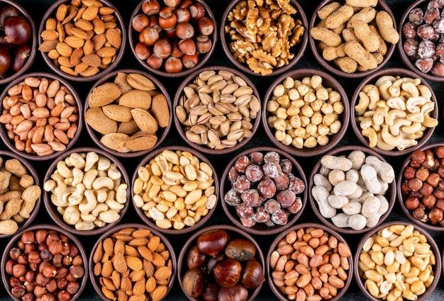 Conjunto de nozes, pistache, amêndoa, amendoim, caju, pinhões e nozes alinhadas sortidas e frutas secas em uma mini tigelas diferentes
