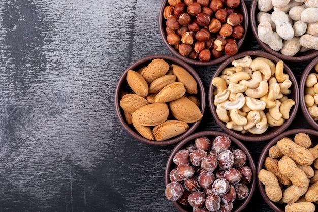 Conjunto de nozes, pistache, amêndoa, amendoim, caju, pinhões e nozes sortidas e frutas secas em uma mini tigelas diferentes