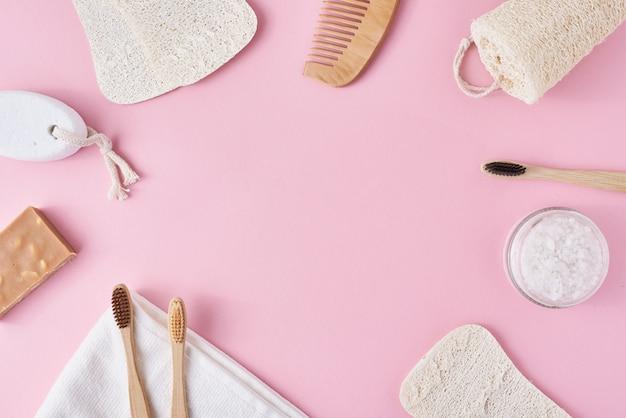Conjunto de objetos de higiene pessoal amigável de eco em um fundo rosa com espaço de cópia. zero resíduos beleza conceito