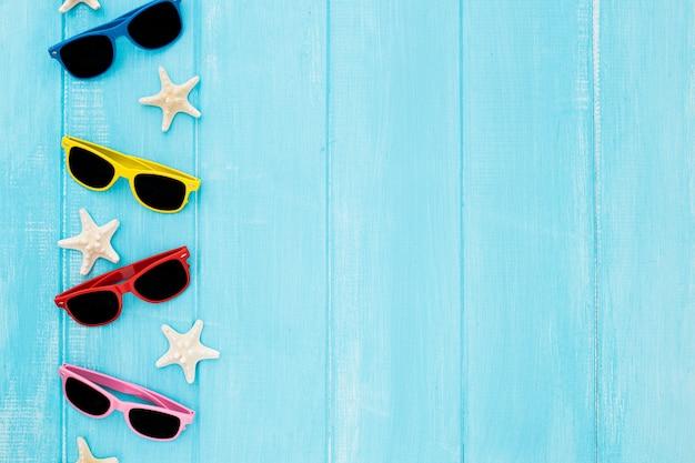 Conjunto de óculos de sol com estrelas do mar sobre fundo azul de madeira