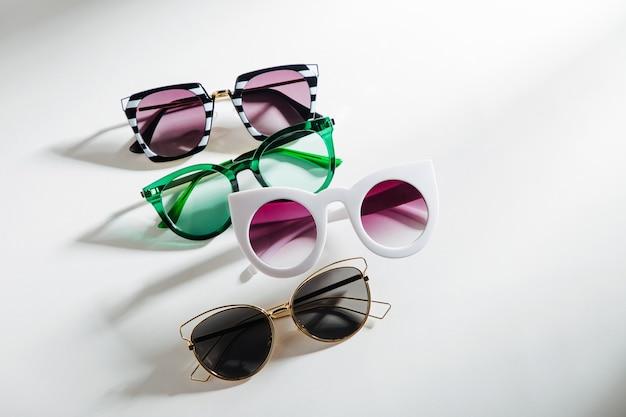 Conjunto de óculos de sol elegantes com luz do sol forte em fundo branco vista de cima plana
