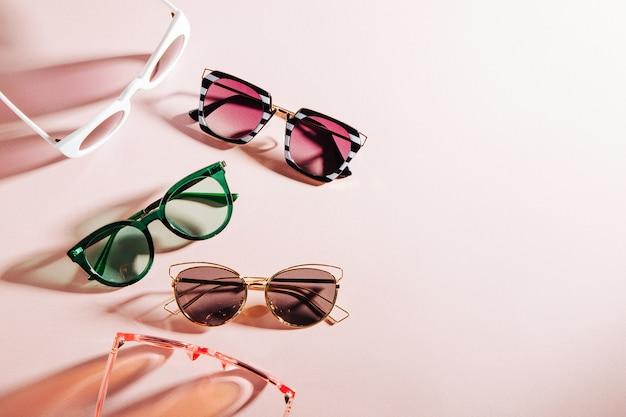 Conjunto de óculos de sol elegantes com luz do sol forte em fundo rosa claro vista superior plana