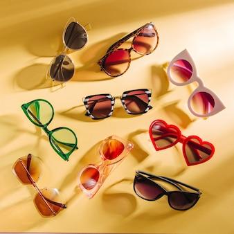 Conjunto de óculos de sol elegantes com luz solar intensa em fundo amarelo vista superior plana