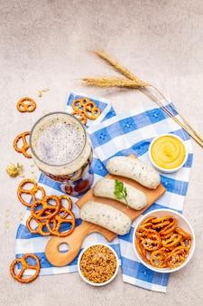 Conjunto de oktoberfest. cerveja escura, weisswurst, pretzels, mostarda, espigas de grãos, lúpulo