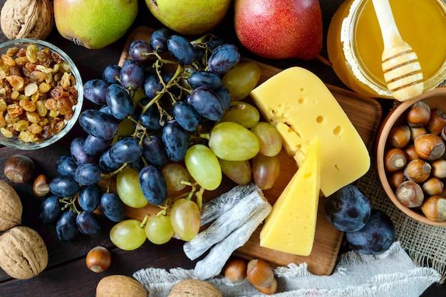 Conjunto de outono de produtos uvas nozes avelãs ameixas mel queijo passas peras cranberries secas na mesa de madeira