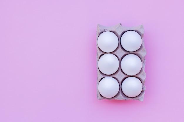 Conjunto de ovos brancos em um fundo rosa