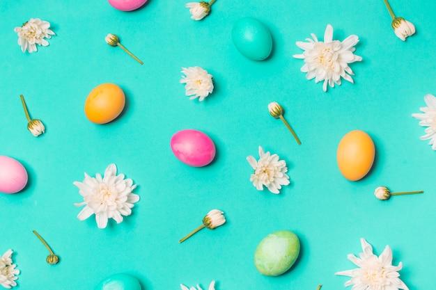 Conjunto de ovos brilhantes entre botões de flores