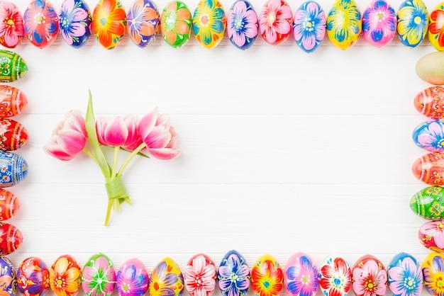 Conjunto de ovos coloridos nas bordas e flores