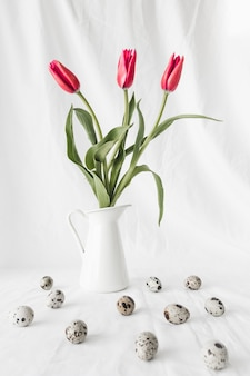 Conjunto de ovos de codorna páscoa perto de flores em vaso