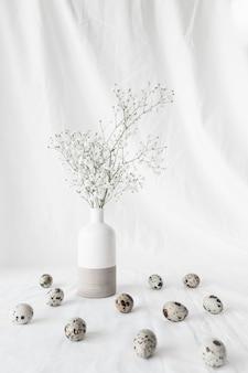 Conjunto de ovos de codorna páscoa perto de ramos de plantas em vaso