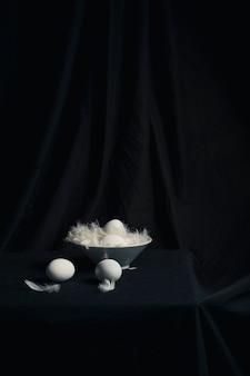 Conjunto de ovos de galinha entre penas na tigela na mesa
