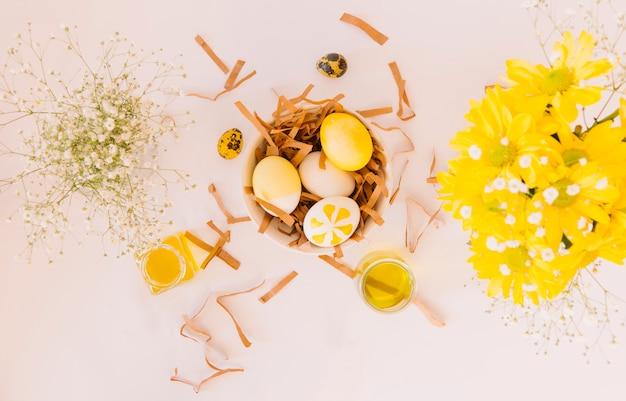 Conjunto de ovos de páscoa amarelos na tigela entre flores frescas e latas de líquido corante