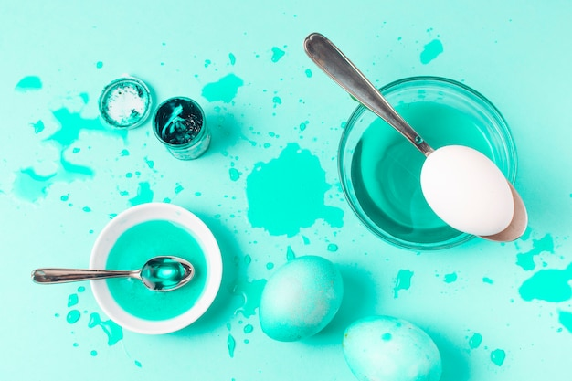 Conjunto de ovos de páscoa azure entre borrões, colher e líquido de tintura Foto gratuita